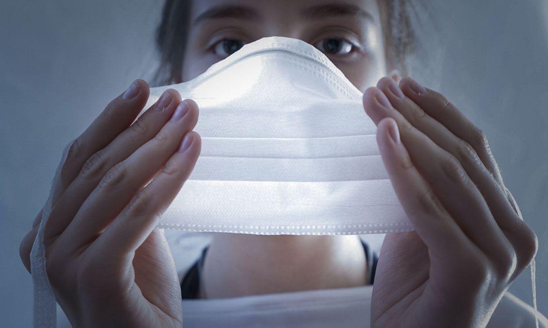 imagem de uma mulher segurando uma máscara