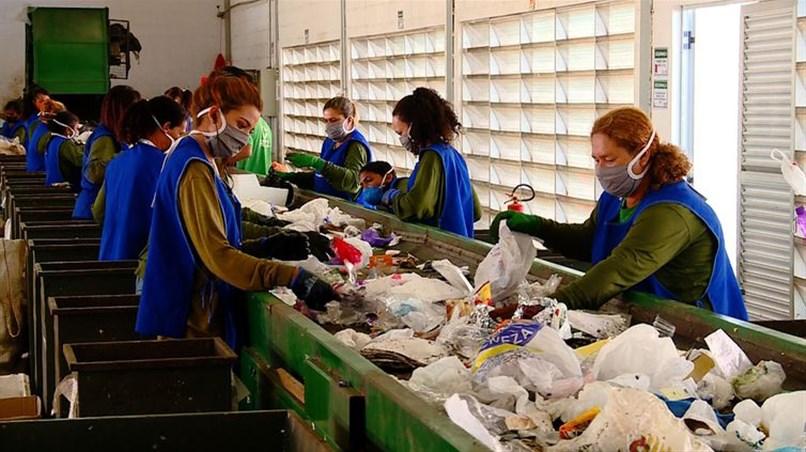 Imagem de pessoas separando material para reciclagem