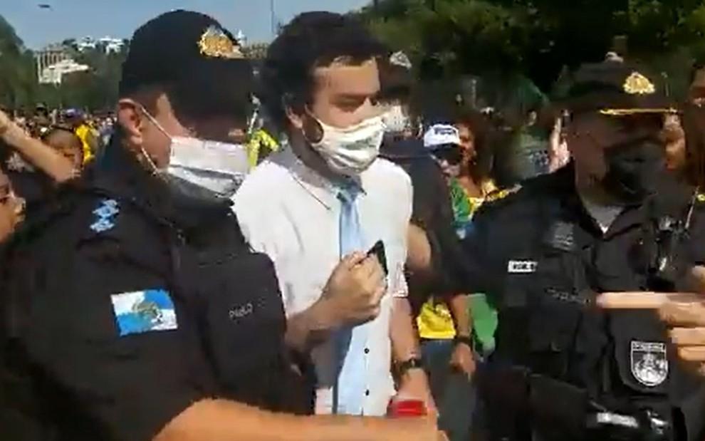 Repórter Pedro Duran sendo escoltado por PMs