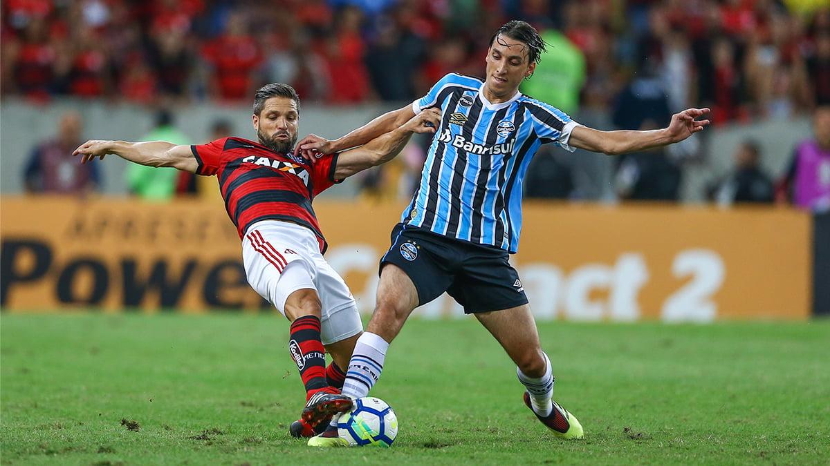 Pedro Geromel,em destaque na disputa de bola com Diego, é um dos desfalques do Grêmio para enfrentar o Flamengo pelo Campeonato Brasileiro