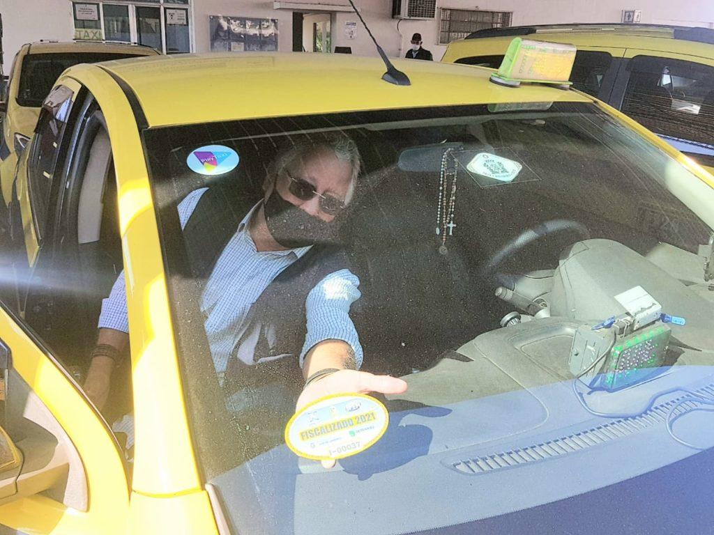 Imagem do deputado Dionísio Lins colocando selo em um táxi