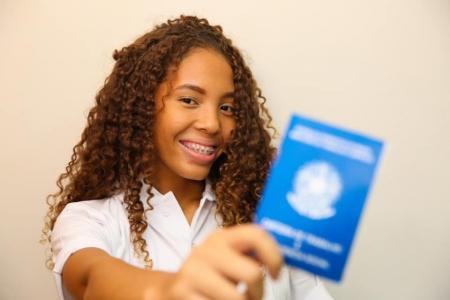 Jovem segura carteira de trabalho