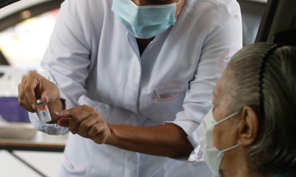 Profissional da saúde mostra seringa a paciente durante campanha