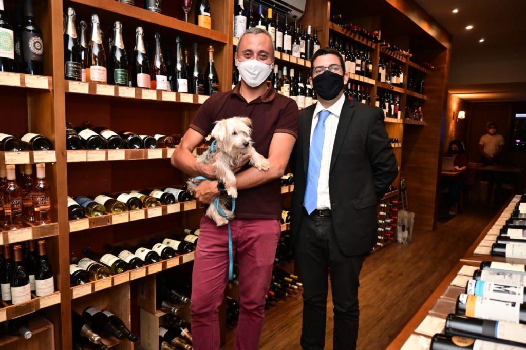 Imagem  do Secretário de Agricultura Marcelo Queiroz com um cliente na loja de vinhos com um cachorro no colo